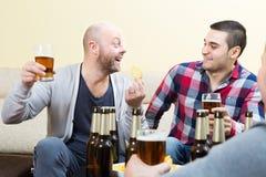 Trois amis heureux buvant de la bière Photographie stock