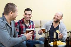 Trois amis heureux buvant de la bière Photographie stock libre de droits