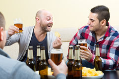 Trois amis heureux buvant de la bière Photos stock