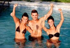Trois amis heureux dans la piscine Photographie stock libre de droits