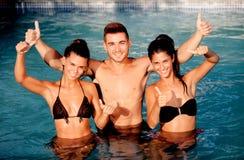 Trois amis heureux dans la piscine disant correct Images stock