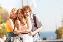 Trois amis heureux des jeunes extérieurs Photographie stock libre de droits
