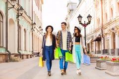 Trois amis heureux marchant avec des paniers Image libre de droits