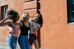 Trois amis heureux marchant dehors Images libres de droits