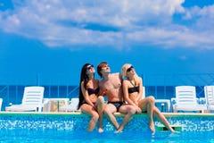 Trois amis heureux par la piscine Photographie stock