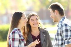 Trois amis heureux parlant dans la rue Photos stock