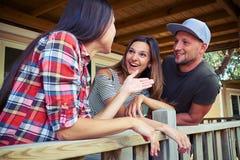 Trois amis heureux se tenant sur la terrasse et la causerie Photos stock