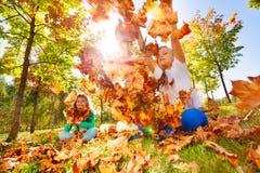 Trois amis jouant avec des feuilles dans la forêt Image stock