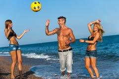 Trois amis jouant avec la bille sur la plage. Photographie stock