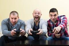 Trois amis jouant des jeux vidéo Photographie stock