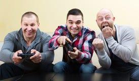 Trois amis jouant des jeux vidéo Photos libres de droits