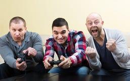 Trois amis jouant des jeux vidéo Photographie stock libre de droits