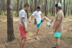 Trois amis jouant le football dans la forêt Photographie stock libre de droits