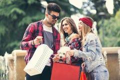 Trois amis jugeant les paniers colorés disponibles Images stock