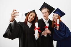 Trois amis licenciés d'international se réjouissant dans les manteaux faisant un selfie à un téléphone Futurs spécialistes ou méd Photographie stock libre de droits