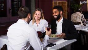 Trois amis mangeant au restaurant Image libre de droits