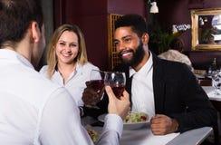 Trois amis mangeant au restaurant Images stock