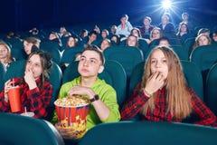 Trois amis mangeant du maïs éclaté en observant le film Photographie stock