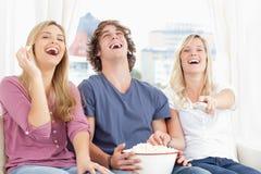 Trois amis mangeant du maïs éclaté tout en riant Image libre de droits