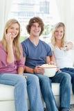 Trois amis mangeant du maïs éclaté tout en souriant   Photographie stock