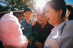 Trois amis mangeant la soie de sucrerie Images stock