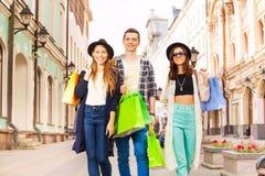 Trois amis marchant avec des paniers sur la rue Image stock