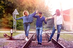 Trois amis marchant sur des voies de train Images stock