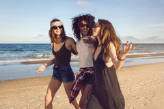 Trois amis marchant sur la plage et rire Photo stock