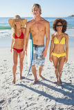 Trois amis marchant vers le bas sur la plage Photos libres de droits