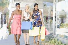 Trois amis marchent côte à côte dans le centre commercial Photos libres de droits