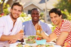 Trois amis masculins appréciant le repas à la partie extérieure Image libre de droits