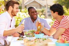 Trois amis masculins appréciant le repas à la partie extérieure Photos libres de droits