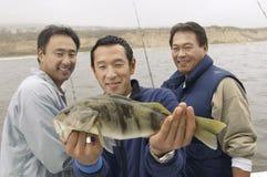 Trois amis masculins avec un crochet Image stock