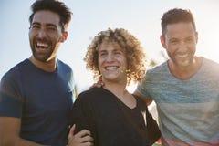 Trois amis masculins beaux riant ensemble dehors Image stock
