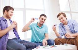 Trois amis masculins de sourire jouant des cartes à la maison Photos stock