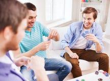 Trois amis masculins de sourire jouant des cartes à la maison Photo stock