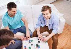 Trois amis masculins de sourire jouant des cartes à la maison Image stock