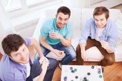 Trois amis masculins de sourire jouant des cartes à la maison Images libres de droits