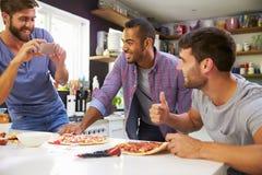 Trois amis masculins faisant la pizza dans la cuisine ensemble Images stock