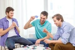 Trois amis masculins heureux jouant le tisonnier à la maison Image libre de droits