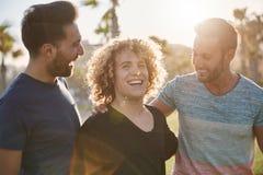 Trois amis masculins heureux riant ensemble dehors Image stock