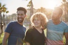 Trois amis masculins heureux tenant l'extérieur regardant loin Photos stock