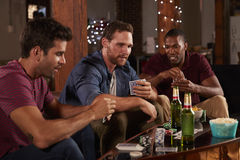 Trois amis masculins jouant des cartes et buvant de la bière à la maison Photo stock