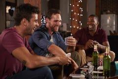 Trois amis masculins jouant des cartes et riant à la maison Image stock