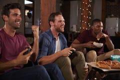 Trois amis masculins jouant des jeux vidéo et mangeant à la maison Image stock