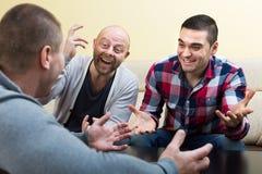 Trois amis masculins parlant à la maison Photos stock