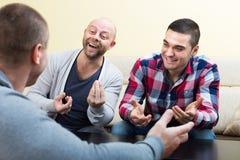 Trois amis masculins parlant à la maison Photographie stock