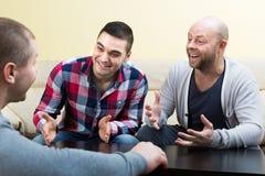 Trois amis masculins parlant à la maison Photo stock