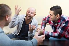 Trois amis masculins parlant à la maison Image stock