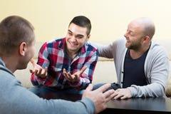 Trois amis masculins parlant à la maison Photo libre de droits